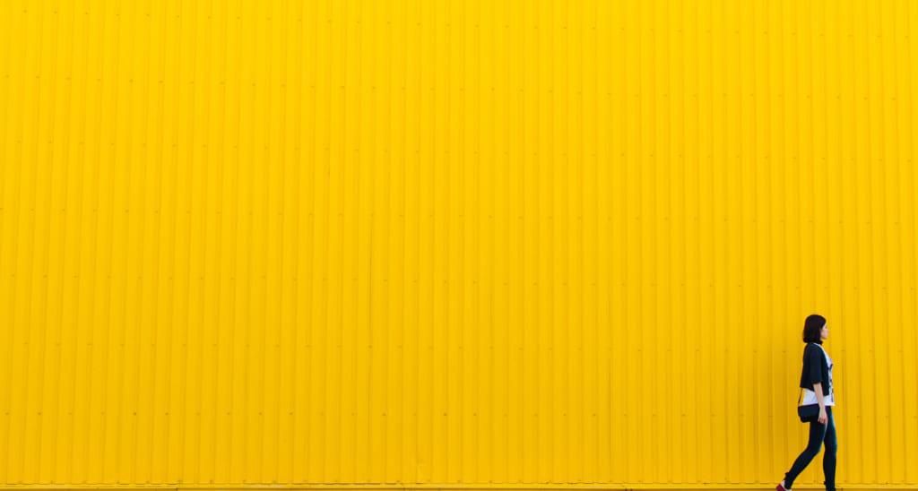 黄色い壁の前を歩く女性